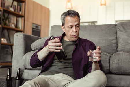Man incomprehensibly looking. Boozy grey-haired old man sitting on floor and flooding his grief with big amount of alcohol