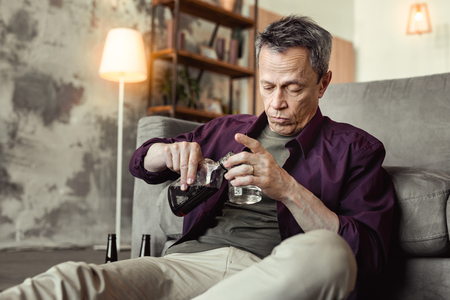 Sitting on floor. Concentrated drunk man pouring dark alcohol in empty glass while leaning on couch alone