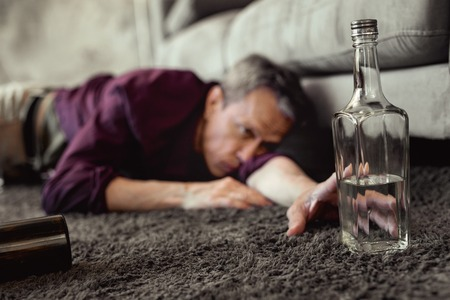 Extreme form. Desperate pity adult man reaching out for half-empty bottle of vodka while mindlessly lying on floor Stok Fotoğraf