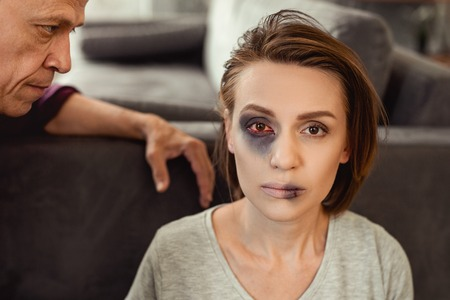 Repeated attack. Dark-haired lady sitting on floor and showing her ruined face with bruised eye and break lips
