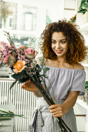 First job. Young beautiful curly red-haired student loving her first job while working in floral shop