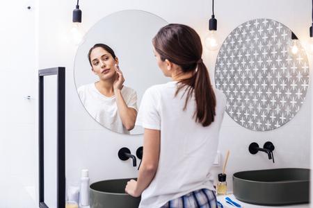 Care of skin. Woman wearing nice comfy pajamas taking care of her skin while using moisturizing toner Stock Photo