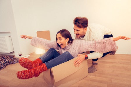 Going crazy. Couple going crazy after unpacking boxes with clothes in new apartment
