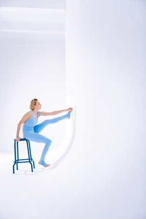 Professional sportswoman. Attractive well built woman sitting near the wall on the stool while having her training