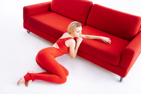 Graceful pose. Beautiful magnetic woman looking in front of her while sitting in a graceful pose near the sofa