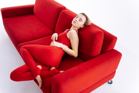 Great comfort. Attractive fit woman having enjoying her comfort while having rest on the sofa