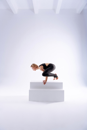 Gymnastic skills. Attractive flexible woman showing her great skills while putting her body up in the sitting pose