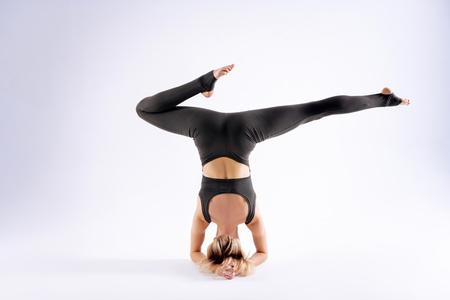 Allenamento acrobatico. Donna bionda magra che muove le gambe in aria mentre fa un allenamento acrobatico