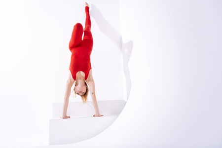 Beautiful and fit. Strong beautiful woman training her muscles while standing on her hands near the wall