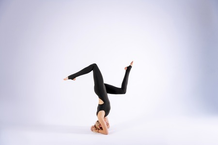 Special skills. Skilled female acrobat standing upside down while having her training