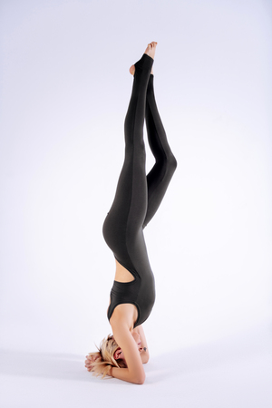 During the sports training. Attractive skinny woman standing on the floor upside down while having her training