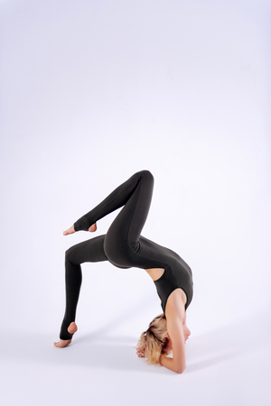 Flexible gymnast. Attractive skinny woman doing a backbend while showing a professional somersault Banque d'images
