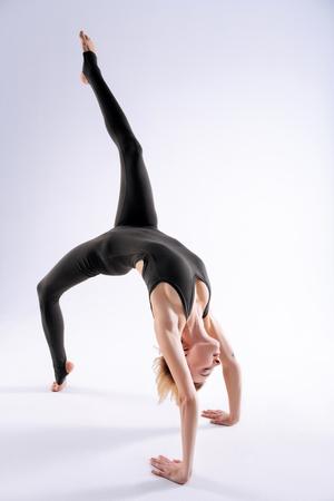 Acrobatic skills. Beautiful female acrobat raising her leg up while doing a somersault