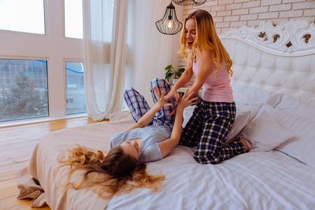 Having much fun. Two cheerful good-looking sisters wearing nice pajamas having much fun in the bedroom