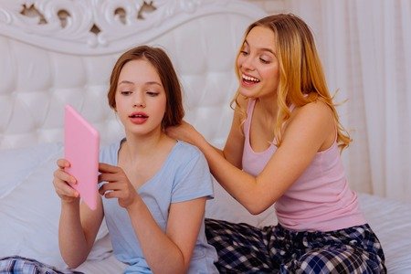 Showing dress. Younger sister shopping online and showing the dress while older sister doing hairstyle in bedroom