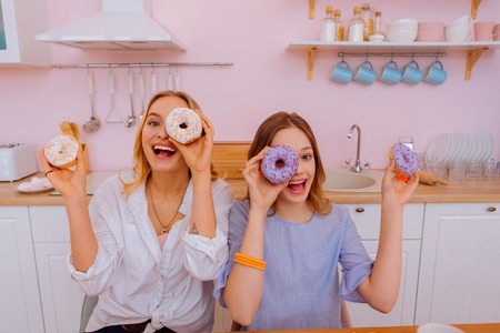 Doughnuts near faces. Two siblings having fun and laughing while having doughnuts near faces
