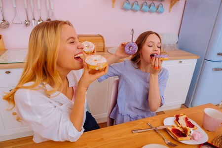Laughing with doughnuts. Blonde-haired sister laughing while eating doughnuts with funny teenage sibling