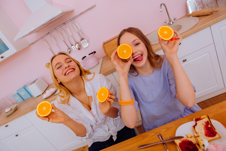Feeling amazing. Two beaming happy sisters holding oranges feeling amazing having breakfast together