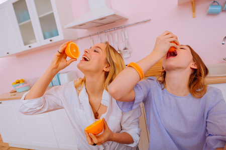 Orange juice. Funny lovely beautiful sisters squeezing orange juice into mouths during breakfast 版權商用圖片