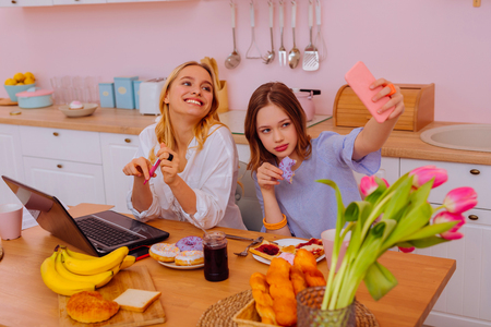 Posing for photo. Beaming blonde-haired student posing for photo with cute teenage sibling in the kitchen