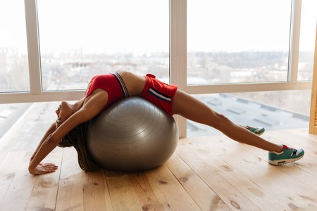 Stretching back. Slim active woman stretching her back on fitness ball near the window at home Reklamní fotografie - 120571901