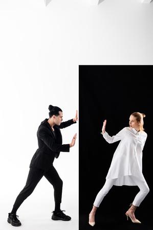 Modelos en imágenes. Modelos con estilo profesionales posando en imágenes de yin y yang cerca de fondo blanco y negro Foto de archivo