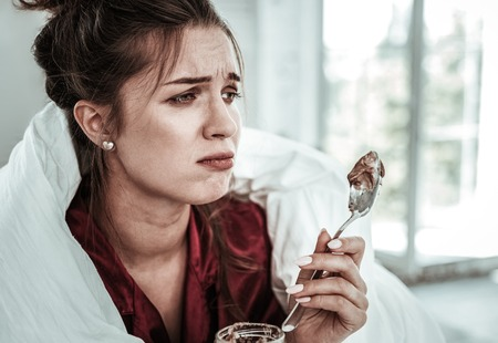 Being stressed. An upset woman holding a spoon of dessert
