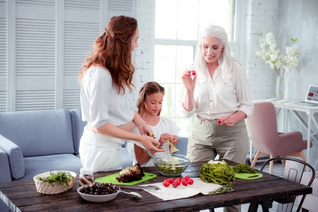 Woman helping. Grey-haired elderly woman helping her pregnant daughter cooking salad standing near granddaughter