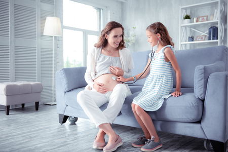 Doctor game. Cute little girl feeling involved in playing doctor game with her beautiful pregnant mom 版權商用圖片