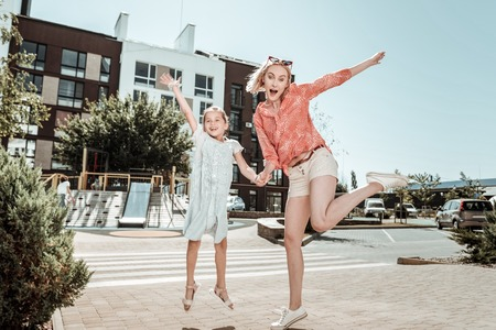 Absolute fun. Joyful nice mother and daughter holding hands while jumping together