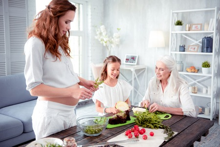 Cooking garden salad. Pregnant woman wearing white trousers cooking garden salad with mom and daughter Archivio Fotografico