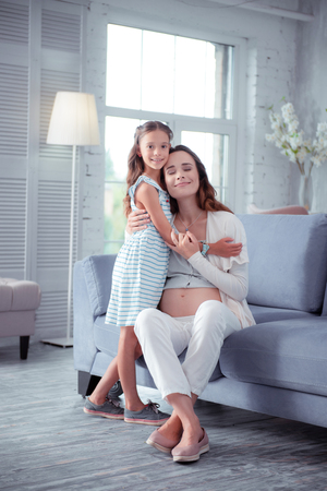 Extremely happy. Pregnant woman feeling extremely happy spending time with older daughter