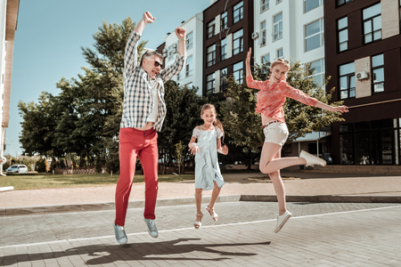 Family day. Joyful happy family jumping while having fun together
