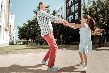 Loving father. Positive delighted man smiling while playing with his daughter 写真素材