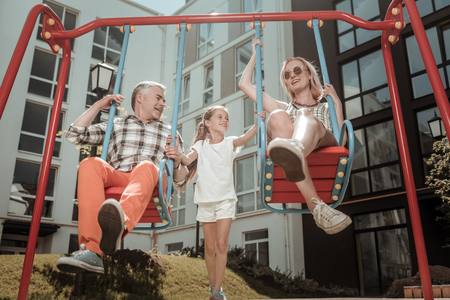 Like in childhood. Happy delighted parents sitting on the swings while having fun with their daughter
