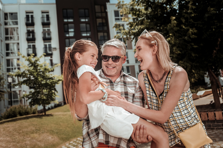 Happy emotions. Joyful positive man holding his daughter while enjoying time with his family