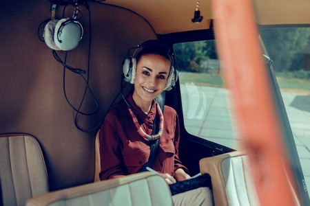 Traveling on the helicopter. Joyful attractive woman being busy while sitting on the back seat of her helicopter