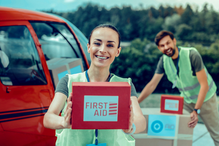 Excited dark-haired woman presenting red box with first aid medicines while planning important flight