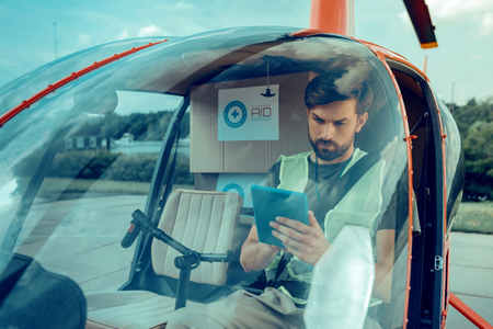 Information about delivery. Attentive serious guy with black bearded sitting in the helicopter and working with the tablet