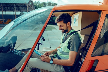 Good-looking man. Concentrated short-haired man checking planed rout on his tablet while sitting in helicopter