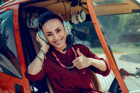 Bella pilota femminile allegra che mostra una miniatura ed esprime felicità mentre è seduta in elicottero