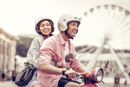 Positive delighted woman smiling while holding on to her boyfriend