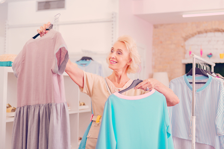 A middle-aged woman choosing among two dresses in the boutique Stockfoto