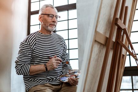 Holding painting brush. Bearded artist wearing bracelet holding painting brush while looking on canvas Stock Photo