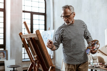 Mixing colors. Bearded famous grey-haired artist mixing some colors while painting new landscape