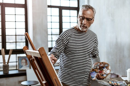 Light workshop. Bearded professional artist wearing glasses working in light spacious workshop Stock Photo
