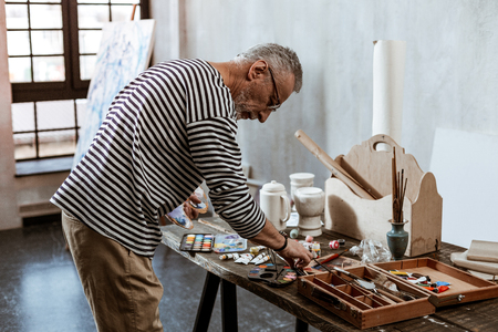 Table with paints. Professional experienced artist standing near the table with paints before starting painting Stock Photo
