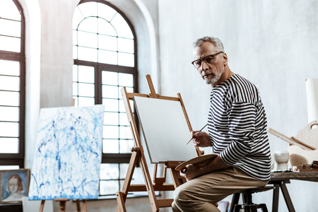 In big workshop. Professional famous artist wearing striped shirt sitting and painting in big workshop