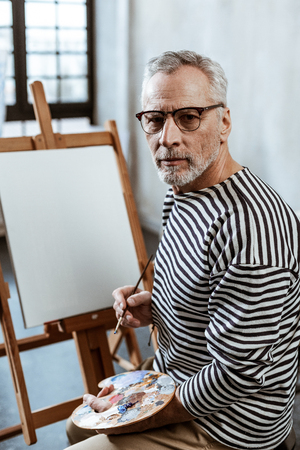 Using gouache. Professional grey-haired artist wearing glasses using gouache while painting on big canvas