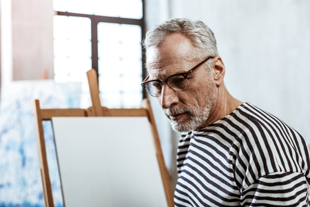 Mature artist. Close up of mature grey-haired artist wearing glasses standing near canvas